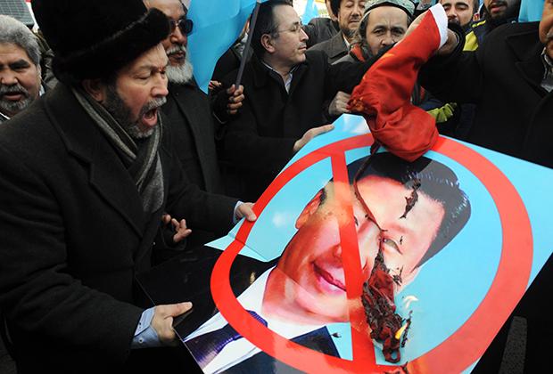 Уйгуры с испорченным плакатом Си Цзиньпина на акции протеста в Анкаре в 2012 году