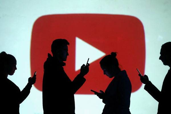 Silhouettes of mobile users are seen next to a screen projection of Youtube logo in this picture illustration taken March 28, 2018.  REUTERS/Dado Ruvic/Illustration