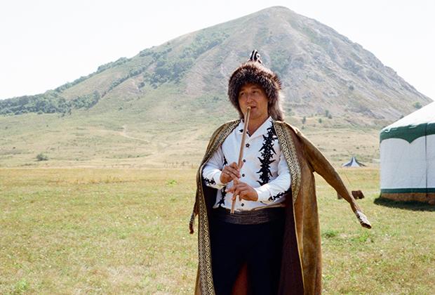Мужчина в национальном башкирском костюме играет на курае