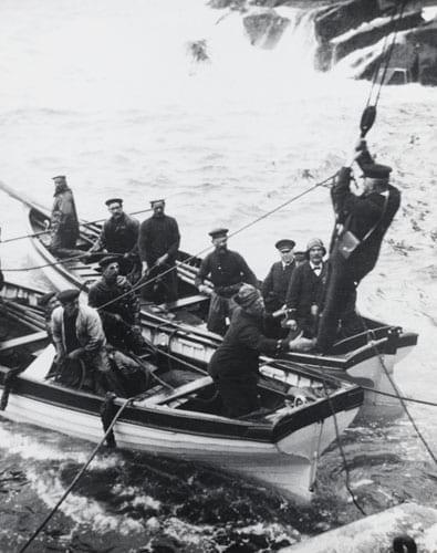 Один из смотрителей маяка спускается в лодку