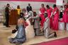 Один из самых важных моментов свадебной церемонии — получение благословения от священника. Крестные жениха и невесты стоят на коленях рядом с ними в этот ответственный момент.