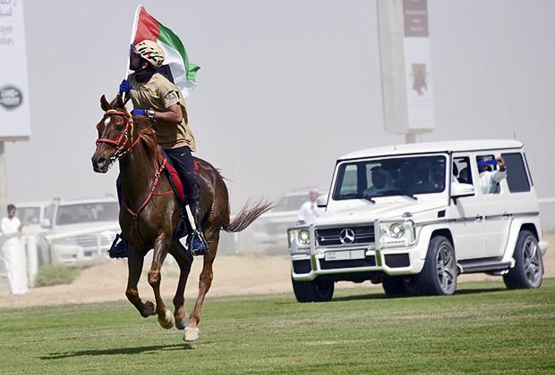 Кронпринц Хамдан бин Мохаммед бин Рашид аль-Мактум целует национальный флаг Дубая, 6 марта 2014 года