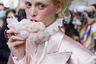 Эта посетительница показа Philosophy всерьез увлеклась трендами прошедших лет. Однако если сегодня большинство поклонников моды отдают предпочтение нарядам из позапрошлого десятилетия, в своем выборе девушка перепрыгнула назад сразу на несколько веков. В сложном образе она соединила высокий парик, популярный в Европе в XVIII веке, розовый атласный костюм и рубашку с воротником жабо. Завершением наряда стал яркий макияж и толстый слой белой пудры.