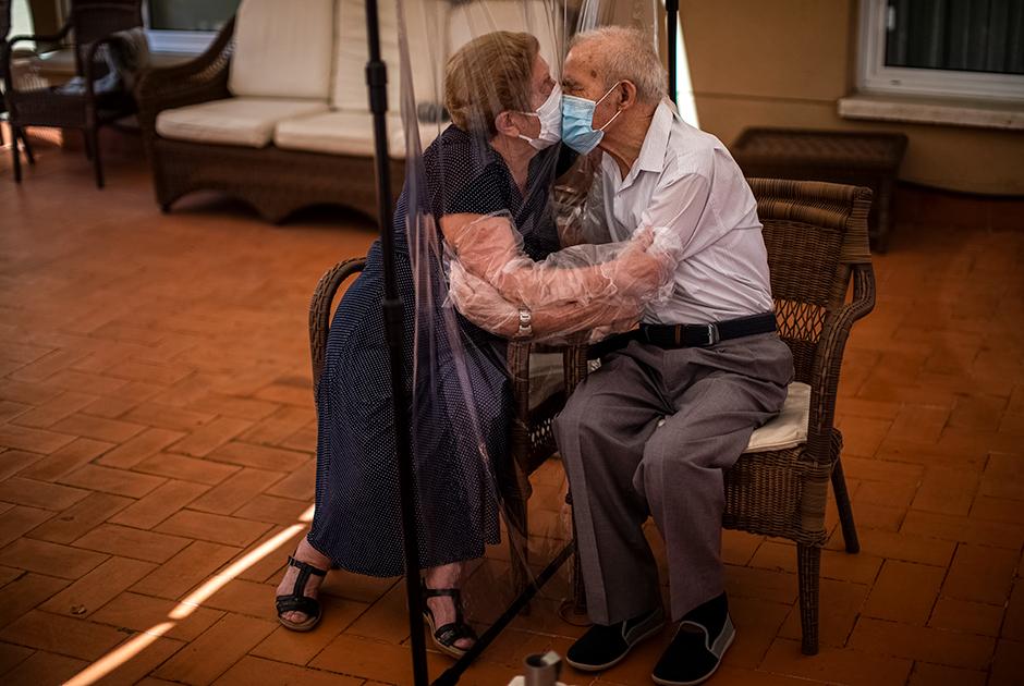 81-летняя Августина и 84-летний Паскаль обнимаются и целуются через пластиковую перегородку в доме престарелых в Испании в июне 2020-го. Из-за пандемии им не разрешали видеться в течение 100 дней