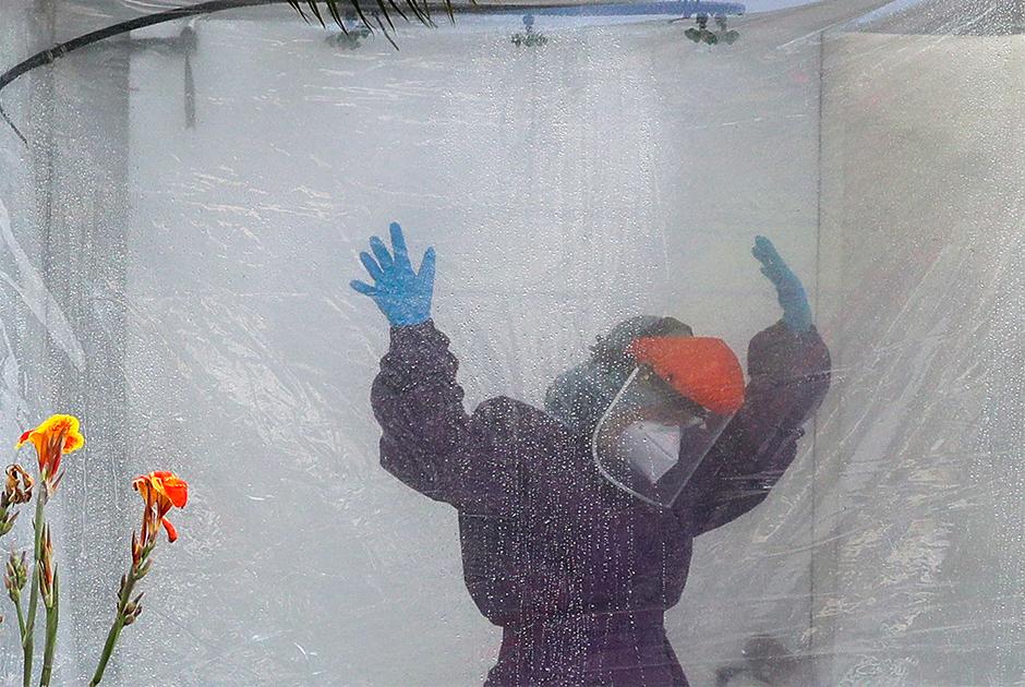 Медработник в филиппинской столице Маниле в защитном костюме во время дезинфекции