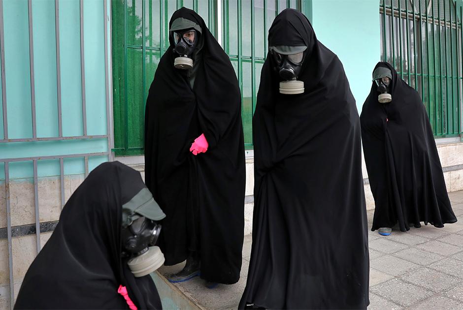Женщины готовят тело умершего от коронавируса к погребению на кладбище на севере Ирана