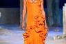 """В показе люксового итальянского бренда Versace приняла участие российская супермодель Ирина Шейк. Она продемонстрировала ярко-оранжевое платье из новой коллекции марки, дизайн которого напоминал наряд из прошлогодней линейки французского дома <a href=""""https://instagram.com/p/B7g8uEcD1QT/"""" target=""""_blank"""">Jacquemus</a>. Последний в соцсетях представляла американская коллега Шейк Белла Хадид. <br> <br> Однако вряд ли зрители шоу заметили подозрительное сходство образов моделей — немалую роль в этом сыграло глубокое декольте и бронзовый загар российской модели."""