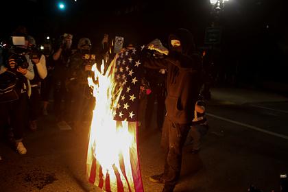 Участник протестов конца сентября в Портленде жжет американский флаг