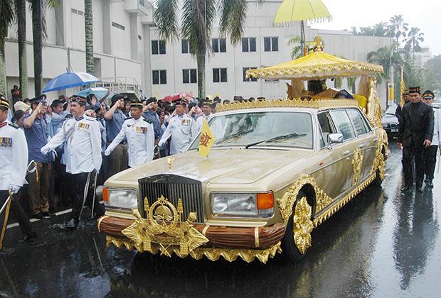 Наследный принц Брунея Аль-Мухтади Биллах и его невеста Сара Пенгиран Саллех проезжают через центр столицы Бандар-Сери-Бегаван на золотом Rolls-Royce после свадебной церемонии, 9 сентября 2004 года