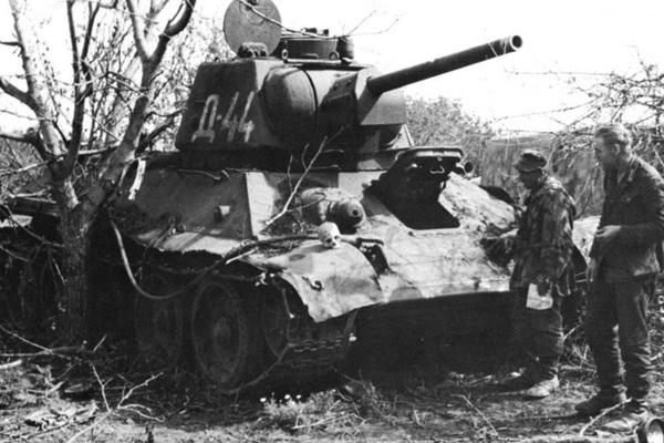 Немецкие солдаты смотрят на человеческий череп на броне огнеметного танка ОТ-34. Латвия, 1944 г.