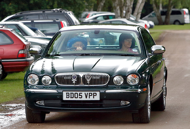 Королева Елизавета II за рулем автомобиля Daimler Jaguar в сопровождении офицера полиции Кэрол Квирк