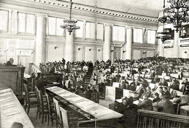 Зал заседаний Государственном Думы в Таврическом дворце. На трибуне депутат произносит речь. На переднем плане — места для министров