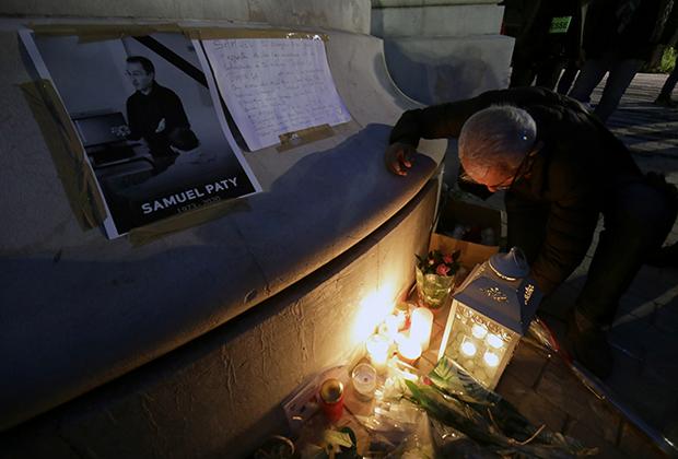 Люди приносят цветы и свечи к мемориалу убитого учителя Самуэля Пати