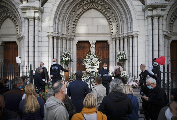 Люди несут цветы в церковь Нотр-Дам-де-Нис