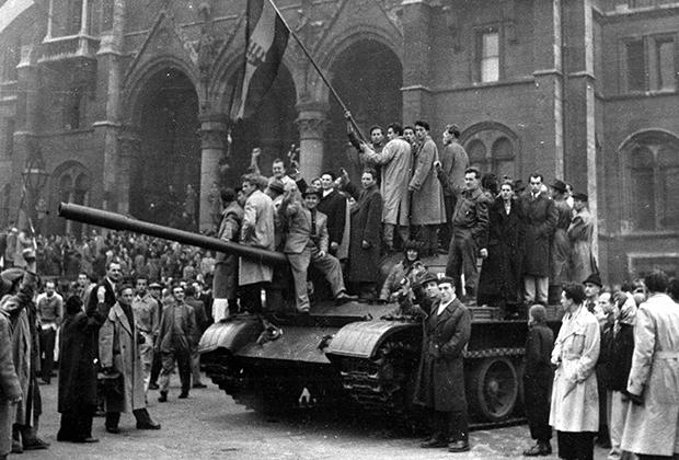 Венгерские демонстранты с флагом Венгрии на захваченном советском танке перед парламентом в Будапеште, 1956 год
