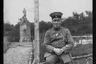 Немецкий офицер с «Железным крестом» и сигарой сидит на заборе возле таблички Бернет Платц. Западный фронт, 1916 год.