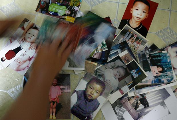 Фотографии пропавших детей в доме одной из матерей из города Дунгуань