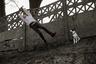 На этом снимке изображен беззаботный подросток, который качается на тарзанке. О том, что действие происходит в промышленном районе, говорит длинный и высокий типовой забор на заднем плане, который со временем практически разрушился.