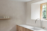 Кухня британского архитектора-минималиста Джона Поусона (John Pawson) больше похожа на столовую. Здесь собрано только самое необходимое для обеда: столешница, раковина, полка для посуды, обеденный стол со стульями, но нет плиты. Отсутствие плиты на этой кухне не связано с забывчивостью архитектора-минималиста, просто в его доме целых три кухни. <br><br>Поусон сделал интерьер максимально простым. Внимание привлекает не только пустота комнаты, но и некоторые элементы — глянцевая белая раковина и металлический смеситель, который выглядит инородно и выбивается из общей концепции. Главные материалы для минималиста Поусона — дерево и бетон, цвет которого напоминает разведенный с водой кефир или штукатурку.