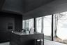 Темно-серый интерьер для сборного дома Shelter («убежище») разработала датская студия Vipp. Кухня с прямоугольной столешницей выдержана в минимализме. Дизайнеры выбрали для нее темные шкафы с длинными ручками и высокую духовку. Значительную часть пространства архитекторы отдали под рабочую зону с плитой и раковиной, но при этом умудрились оставить достаточно места для комфортной готовки.<br><br>Главная особенность кухни — панорамные окна, из которых открывается вид на озеро. Благодаря решению дизайнеров пространство не давит и не выглядит мрачным — стекло дает ему много света и воздуха. Дизайнеры также решили разбавить интерьер металлическими деталями в виде покрытия стола и крышки мусорной урны. Последняя играет особое место в истории компании Vipp.<br><br>Именно с изобретения урны с педалью и началась история Vipp. Компания основана Хольгером Нильсеном (Holger Nielson), который и придумал теперь уже привычный формат «мусорки» для своей жены-парикмахера. Дизайном и архитектурой Vipp занялась только несколько десятилетий спустя.
