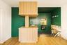 Совсем иной взгляд на пространство представили архитекторы из французского бюро Atelier Sagitta. Для небольшой парижской квартиры в районе Clichy-Batignolles они придумали изумрудную кухню с деревянными панелями из дуба. Полет фантазии авторов одобрил хозяин квартиры — арт-директор из музыкальной индустрии, который перед началом работ попросил привнести в дом «нотку оригинальности».<br><br>Архитекторы решили выкрасить часть стен и фасады в смелый цвет и немного разбавить его спокойным деревянным ярусом, который отдали под столешницы и раковину. Особенность задумки — зона плиты, оформленная в виде отделанной тем же светлым дубом ниши. Весь функционал кухни максимально спрятан за панелями — там и посудомоечная машина, и ящики для бесчисленных венчиков и ложек, и высокий шкаф для посуды и продуктов. Дизайнеры умудрились вписать в интерьер и небольшой обеденный стол, который при желании можно легко разложить.