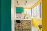 Архитекторы из китайского бюро MDDM Studio придумали яркий интерьер для кухни в пекинской квартире и выкрасили часть стен в желтый цвет. Несмотря на небольшое пространство, они смогли разместить в комнате и четырехконфорочную плиту, и столешницу с рабочей зоной и барной стойкой. Большая часть поверхностей — белая и глянцевая, но есть и яркие элементы в виде бирюзового шкафа и темно-серых барных стульев из текстиля.<br><br>Цвета из буйной палитры сочетаются между собой. Дизайнеры достигают гармонии с помощью каменных панелей тераццо, которые изначально использовались на полах в венецианских интерьерах. На кухне они выделяются под барной стойкой и на стене около плиты, но интерьер не смотрится аляпистым — тераццо соединяет более теплые оттенки главных цветов комнаты, органично создавая единую концепцию.