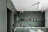 Кухня с трудно различимым оттенком серо-зеленого цвета находится в апартаментах на бельгийском побережье. Ее дизайн разработали местные архитекторы Кармин Ван Дер Линден (Carmine Van Der Linden) и Томас Гелдоф (Thomas Geldof). Они выбрали простую планировку — деревянные шкафы с двумя нишами, в одной из которых стоит варочная поверхность. Рядом — рабочая зона с хромированной раковиной, большая полка для посуды и кулинарных книг, а в центре — стол, который при желании можно использовать как столешницу или барную стойку.<br><br>Гарнитур имеет сложный оттенок, одновременно напоминающий и серый, и зеленый цвета. По задумке Дер Линден и Гелдофа, палитра должна быть напрямую связана с локацией квартиры, поэтому они выбрали для деревянных фасадов цвет мутных водорослей, которые можно увидеть в море неподалеку. На фоне гарнитура выделяется белая мраморная столешница и стол с ножками в виде металлических труб — дизайнеры хотели разбавить интерьер элементами стиля лофт.