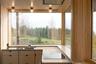 Архитекторы из бюро Sanden + Hodnekvam Arkitekter решили спеть на кухне оду уединению, натуральным материалам и минимализму. Они взяли за основу гарнитура деревянные панели из березы и разбавили их черными акцентами в виде массивных розеток и варочной поверхности. Для пола дизайнеры выбрали светлый бетон, который, несмотря на глянцевый блеск, делает комнату уютной.<br><br>Кухня находится в доме в норвежской губернии Трёнделаг. Ее главная особенность — роскошный вид на фьорд Beitstad и соседний лес. Ради пейзажа архитекторам пришлось пожертвовать верхними шкафами и вмонтировать вытяжку в потолок, чтобы ничего не закрывало обзор. При этом дизайнеры не ограничили место для хранения и просто оборудовали в нижнем ярусе как можно больше ящиков.