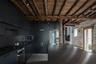 Идею очередного черного дизайна для кухни разработали архитекторы из британского бюро Will Gamble Architects. По всем современным канонам они оборудовали пространство для двух пенсионеров. Локацией послужил сарай бывшей пергаментной фабрики XVII века в английском графстве Нортгемптоншир.<br><br>Кухня выделяется на фоне белой концепции дома с массивными каменными стенами. Особенность ее дизайна — сочетание дерева и металлических поверхностей. Около центральной столешницы с раковиной авторы проекта разместили ствол натурального дерева, который на потолке переходит в массивные балки. Гарнитур со встроенной в нишу микроволновкой полностью покрыт черным цветом с яркими латунными деталями в виде ручек и смесителя. Напротив дизайнеры сделали в стене дверной проем, откуда можно выйти на просторную террасу.