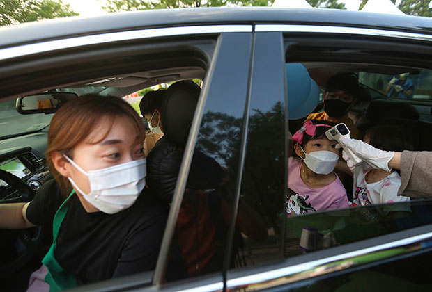 Измерение температуры при въезде на парковку у дворца Кёнбоккун в Сеуле