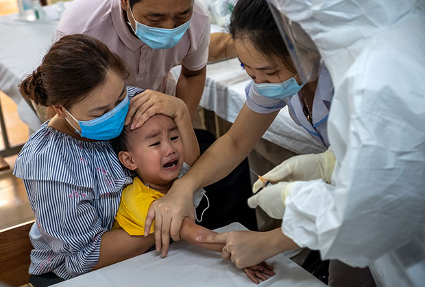 Вьетнамские медики берут у ребенка кровь для анализа на COVID-19