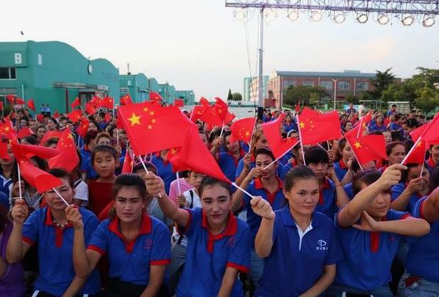 Уйгурские рабочие в учреждении Jiashi Vocational School с китайским флагом