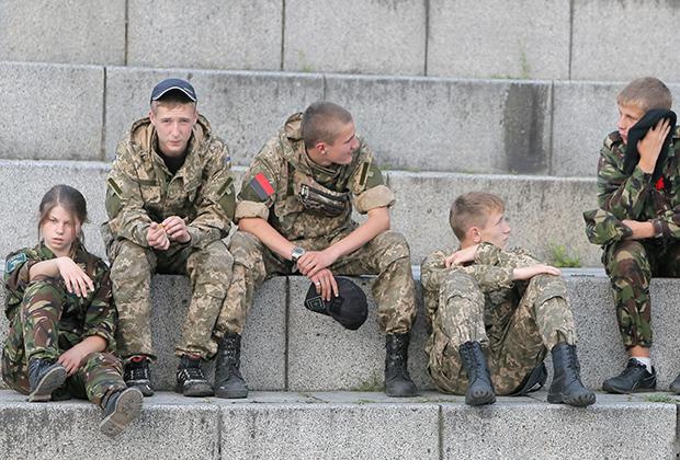 Молодые участники «Правого сектора» отдыхают перед своим митингом в центре Киева, Украина. 21 июля 2015 года