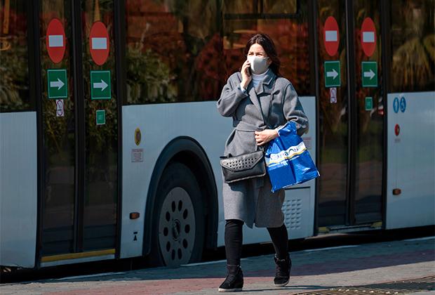 Женщина в защитной маске на автобусной остановке.