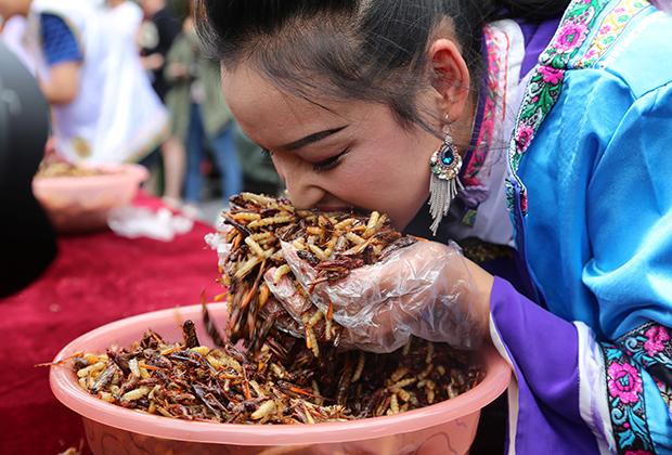 Китаянка принимает участие в соревновании по поеданию насекомых