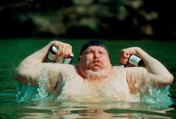 Толстый человек выныривает из воды с пузырьками Гербалайф
