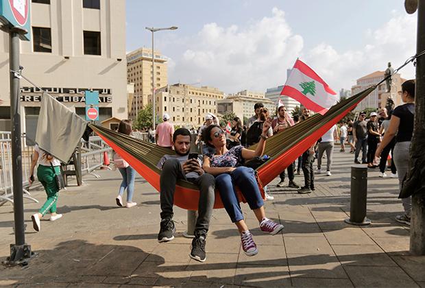 Демонстранты отдыхают в гамаке во время протестов в Бейруте
