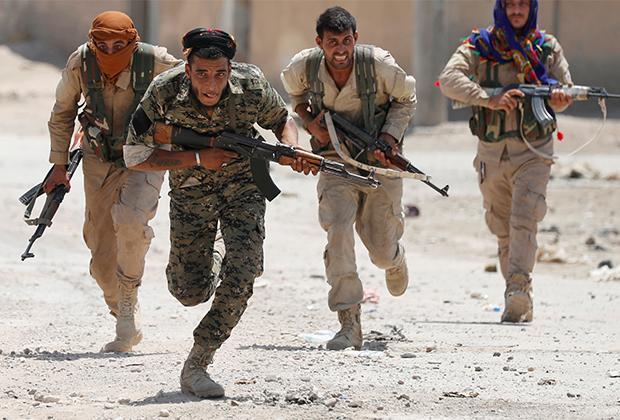 Курдские боевики перебегают улицу в городе Ракке, Сирия