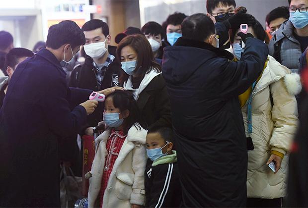 Сотрудники вокзала в Ханчжоу измеряют температуру у людей, прибывших на поезде из Уханя