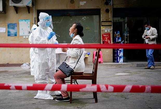 Медработник в защитном костюме делает тест на коронавирус жительнице Уханя