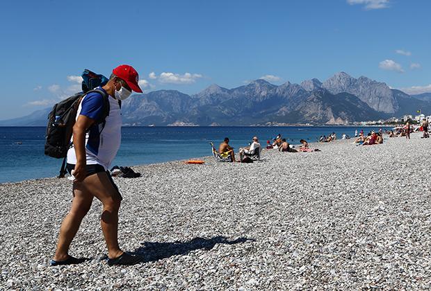 Турист в защитной маске на одном из пляжей Антальи в Турции. Июнь 2020 года