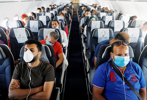 Путешественники в защитных средствах в самолете, вылетающем из Шарм-эль-Шейха