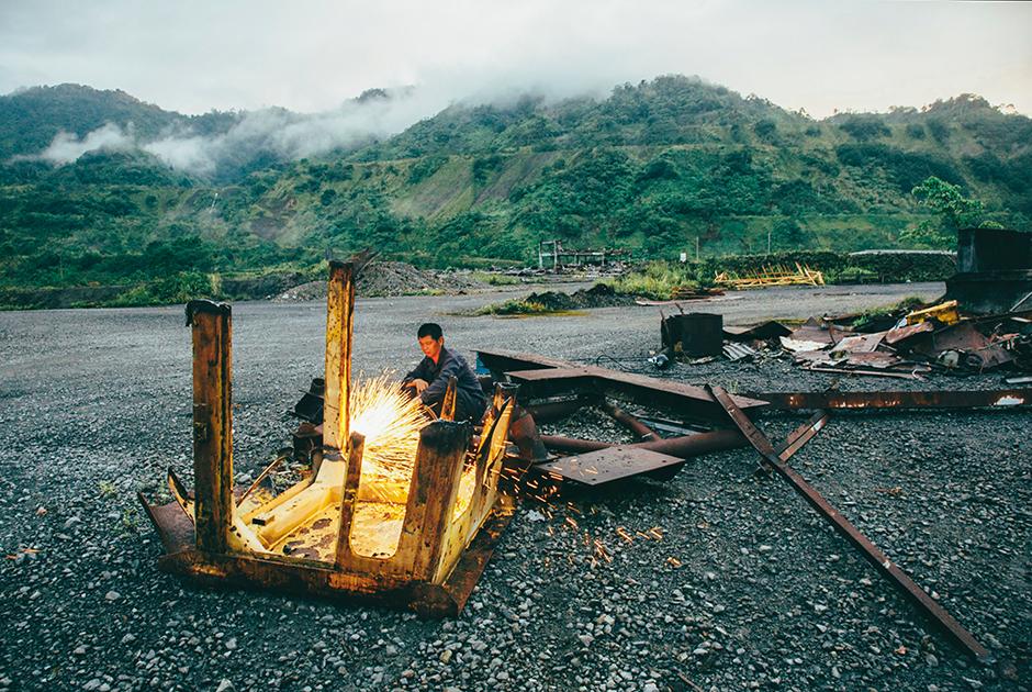 Работник китайской компании по утилизации металла разрезает остатки одной из тяжелых горнодобывающих машин на руднике Пангуна