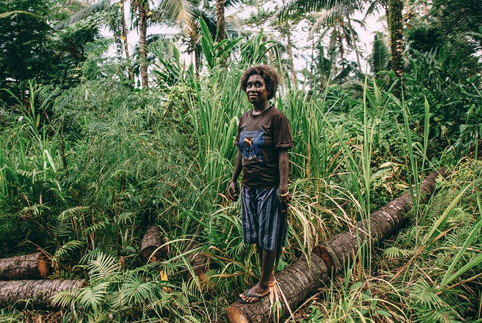Жительница бугенвильской деревни на стволе поваленной пальмы