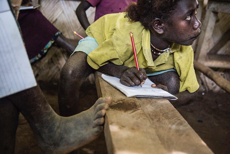 Ученица 3-го класса школы в одной из деревень Бугенвиля записывает школьное задание
