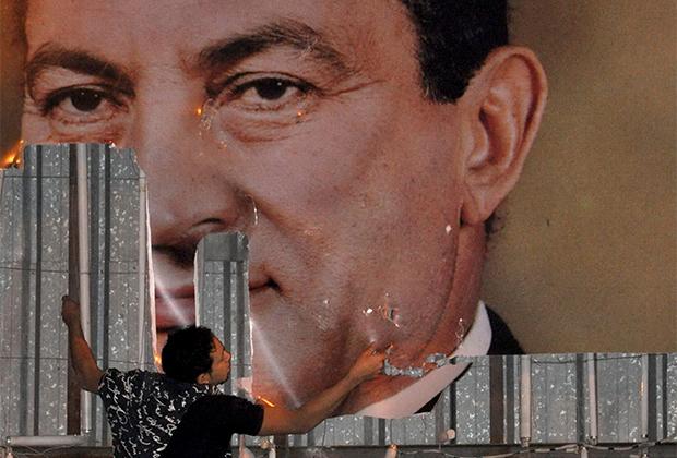 Демонстрант срывает портрет Хосни Мубарака в Александрии