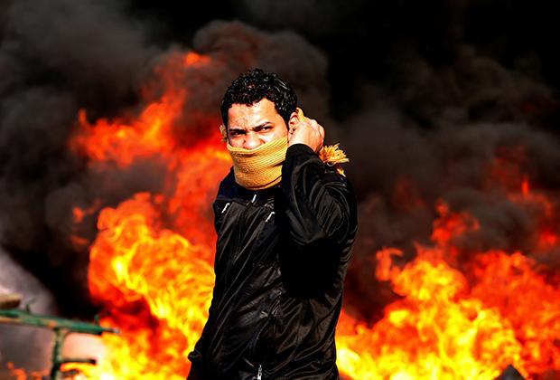 Протестующий у горящих баррикад во время демонстраций в Каире, 28 января 2011 года