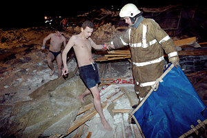 A rescuer helps Transvaal water park visitors wearing only swimsuits  to leave through the debris of its collapsed  roof, in  Moscow, late Saturday, Feb. 14, 2004.  The vast glass roof covering a Moscow water park collapsed Saturday evening, killing at least eight people, injuring nearly 70 and trapping others under the rubble,  according to Russian news agencies. The temperature in  Moscow dropped to minus 17 degrees Celsius (2 degrees Fahrenheit) on Saturday.  (AP Photo/ Anatoly Zhdanov, Komsomolskaya Pravda)