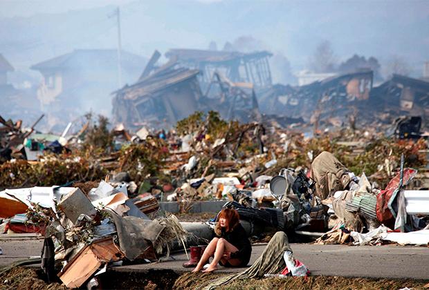 Плачущая женщина на фоне города, разрушенного землетрясением и цунами