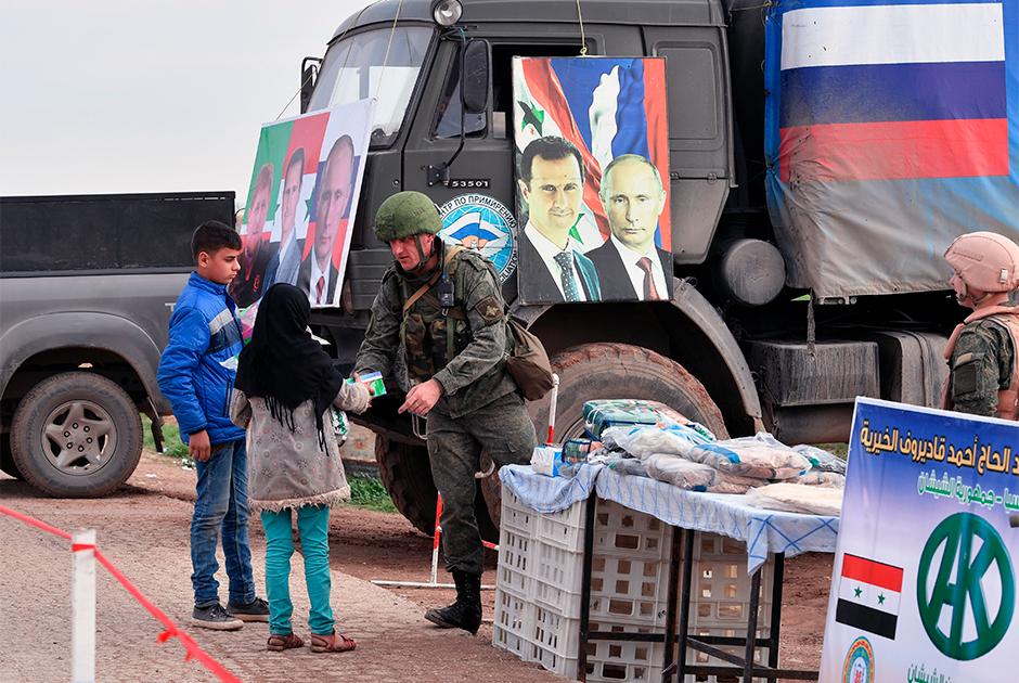 Военнослужащий российского центра по примирению раздает гуманитарную помощь сирийским беженцам в окрестностях провинции Идлиб